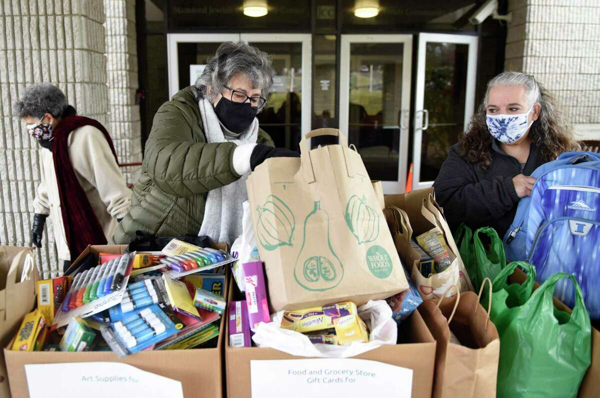 Volunteers Judie Birnbaum, left, and Jami Birnbaum collect donations outside the JCC in Stamford, Conn. Monday, Jan. 18, 2021. Stamford JCC celebrated Martin Luther King Day with a day of service by collecting donations of art supplies for Stamford Public Schools, groceries and grocery store gift cards for New Covenant Center, games and backpacks for DOMUS, winter coats for Person to Person, and winter accessories for Jewish Family Services of Fairfield County.