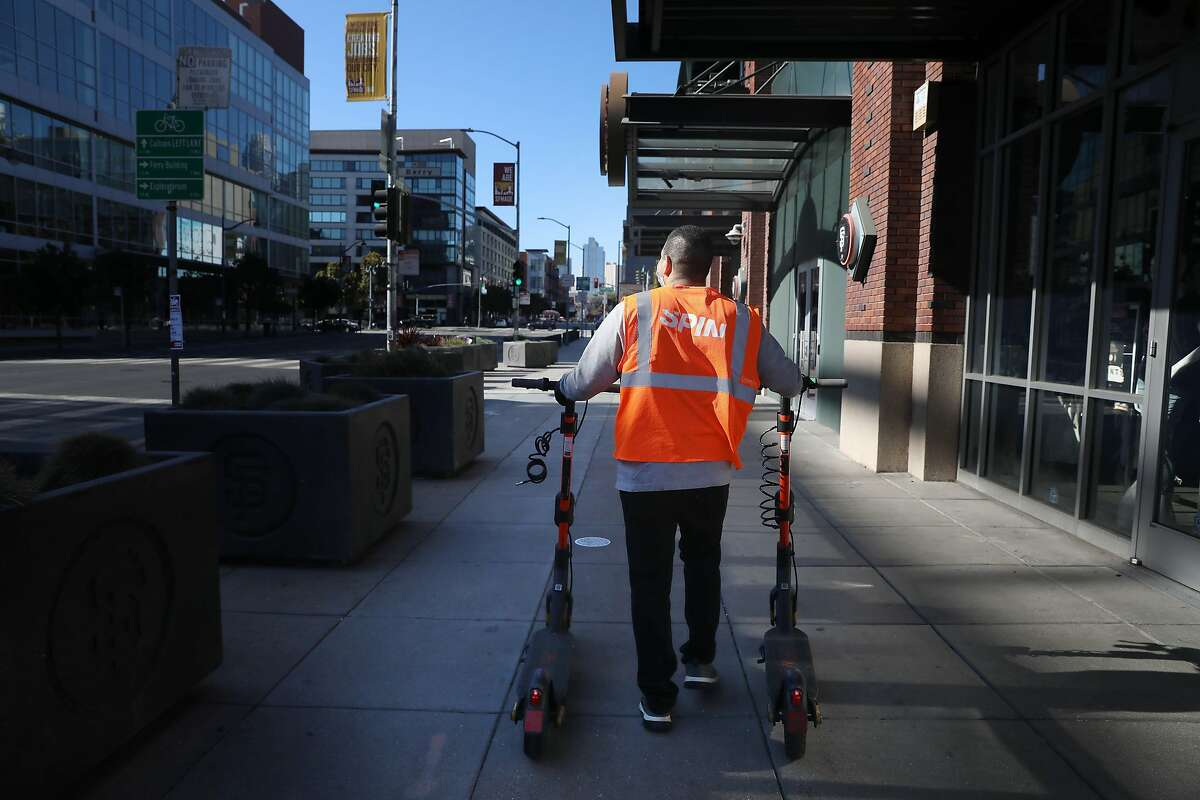 Michael Delgado, Spin operations specialist, walks scooters down Third Street while deploying the electric vehicles near San Francisco's Oracle Park in October.