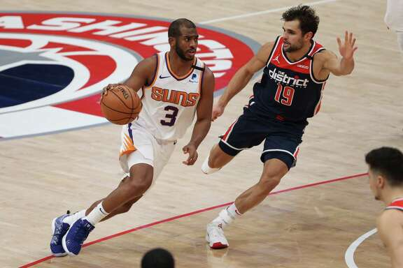 WASHINGTON, DC - JANUARY 11: Chris Paul #3 of the Phoenix Suns dribbles in front of Raul Neto #19 of the Washington Wizards during the second half at Capital One Arena on January 11, 2021 in Washington, DC. NOTE TO USER: User expressly acknowledges and agrees that, by downloading and or using this photograph, User is consenting to the terms and conditions of the Getty Images License Agreement.