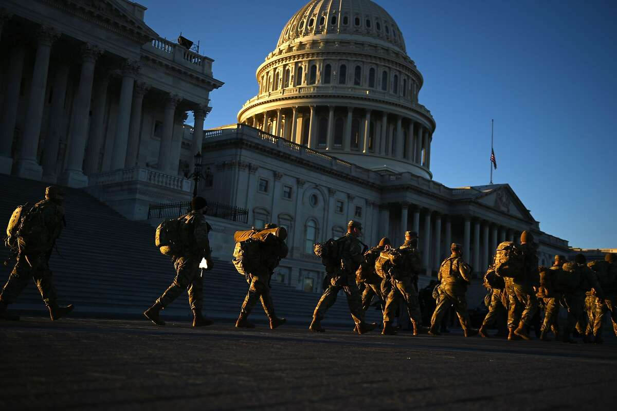 Members of the US National Guard walk past the US Capitol on January 19, 2021 in Washington, DC, ahead of the 59th inaugural ceremony for President-elect Joe Biden and Vice President-elect Kamala Harris. (Photo by Brendan SMIALOWSKI / AFP) (Photo by BRENDAN SMIALOWSKI/AFP via Getty Images)