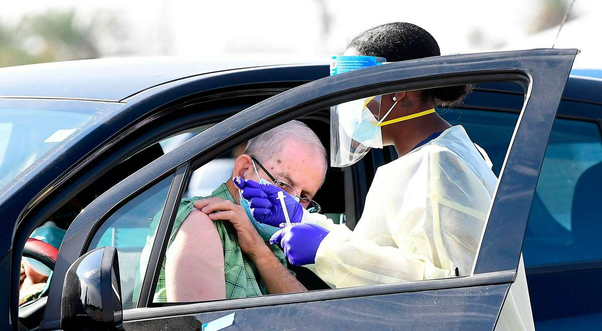 People pull up in their vehicles for Covid-19 vaccines in a parking lot in Inglewood, California on January 19, 2021.