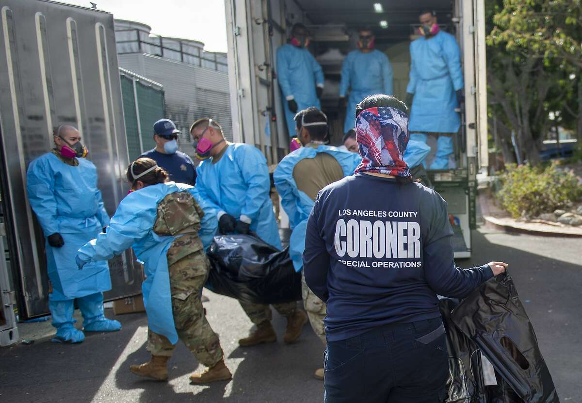 In January 2021, Elizabeth Napoles (right) worked with members of the National Guard to move victims of COVID-19 into temporary storage at the Los Angeles County Medical Examiner-Coroner Office in Los Angeles.