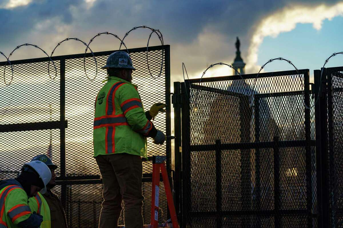 Workers install razor wire atop fencing around the U.S. Capitol in Washington on Monday.