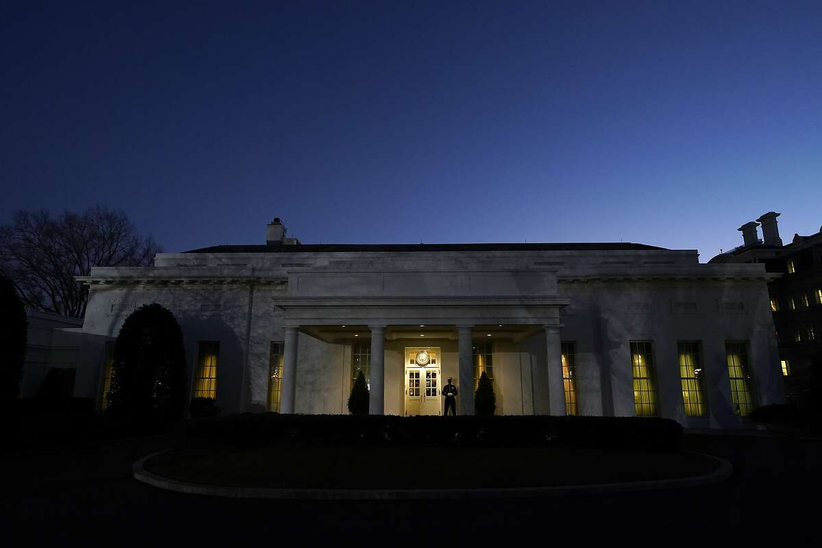 The moon rises over the West Wing of the White House, on President Donald Trump's last day in office, Tuesday, Jan. 19, 2021, in Washington. The Marine guard at the entrance signifies the president is in the Oval Office. (AP Photo/Gerald Herbert)