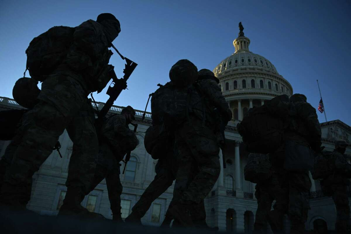 Members of the US National Guard walk outside the US Capitol on January 19, 2021 in Washington, DC, ahead of the 59th inaugural ceremony for President-elect Joe Biden and Vice President-elect Kamala Harris. (Photo by Brendan SMIALOWSKI / AFP) (Photo by BRENDAN SMIALOWSKI/AFP via Getty Images)