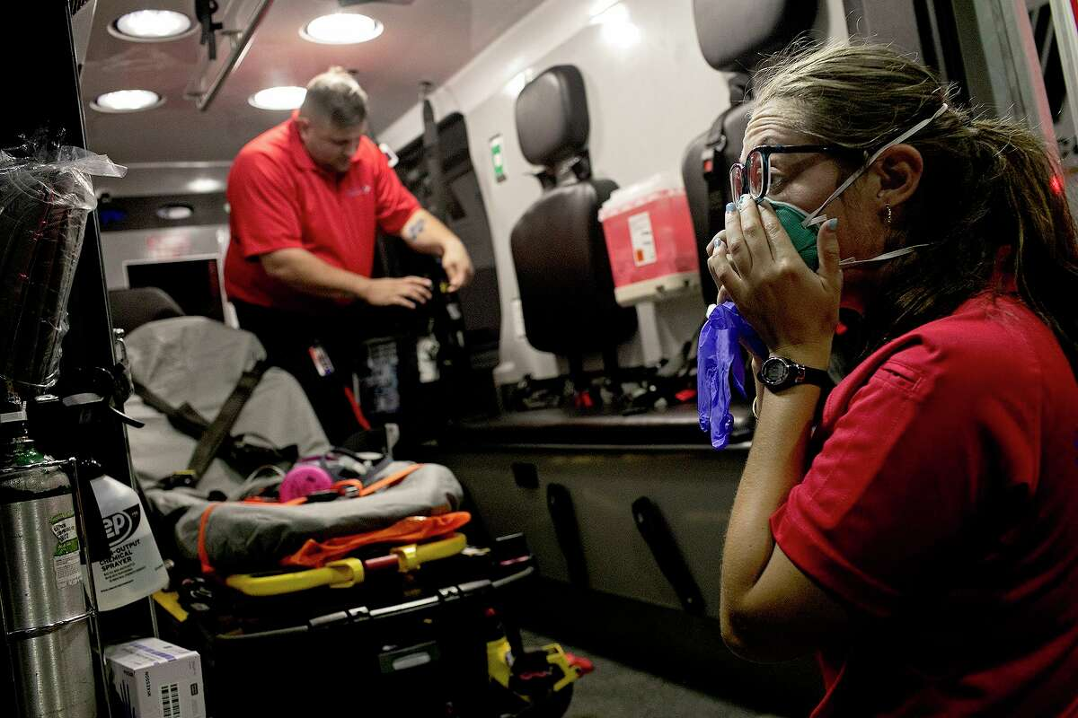 Superior Mobile Health EMT Dominique Sharp puts on extra personal protective equipment as George Lombardo prepares the stretcher to pick up a COVID-19 positive patient from a South Side hospital in July.