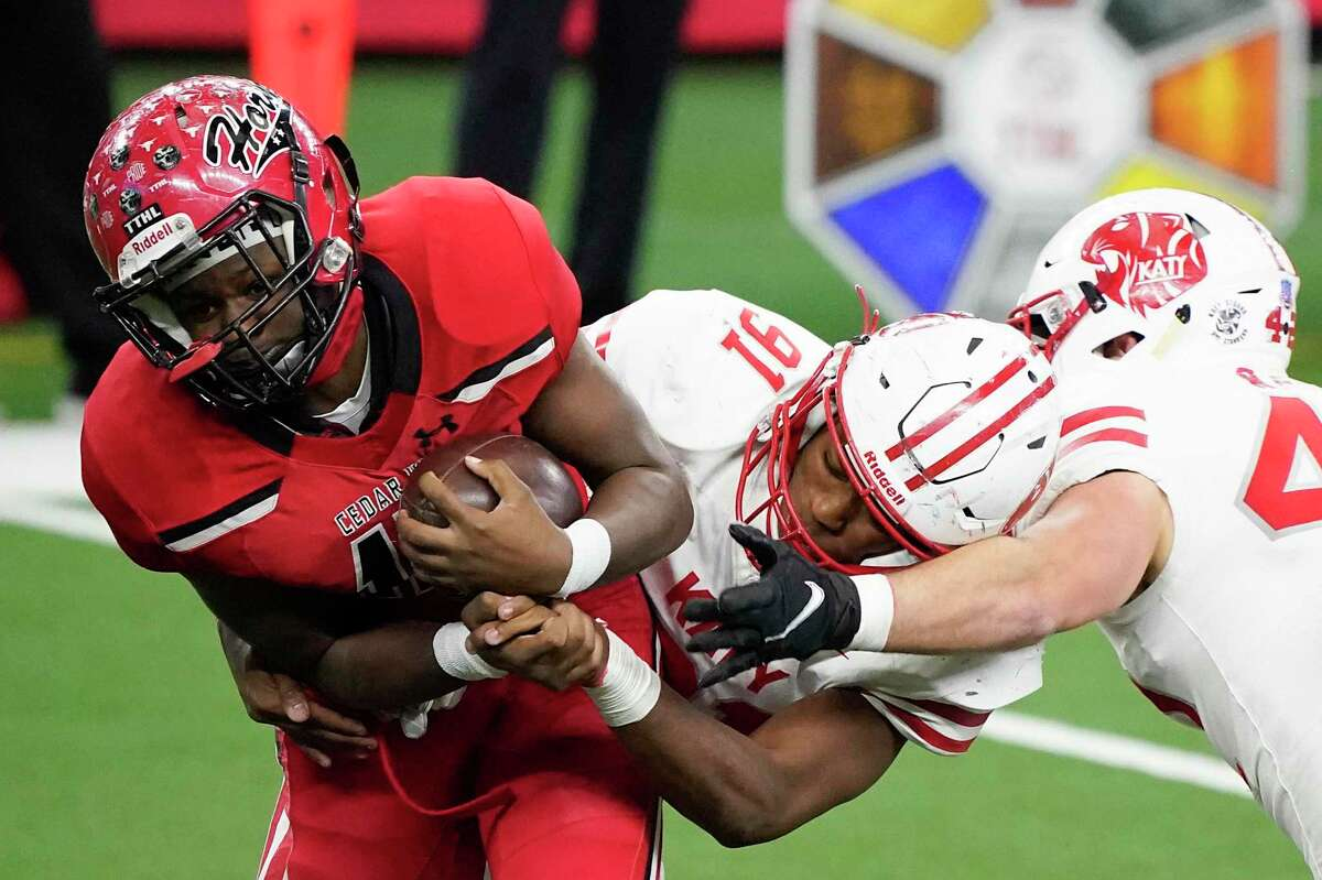 Cedar Hill wide receiver Dewayne Blanton (15) is wrapped up by Katy defensive lineman Cal Varner (91) during the second half of the Class 6A Division II state football championship game Saturday, Jan. 16, 2021, in Arlington, Texas. (Smiley N. Pool/The Dallas Morning News via AP)