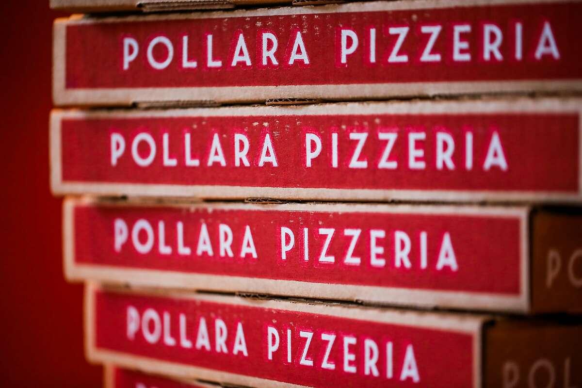 Pollara Pizzeria boxes rest on a shelf.