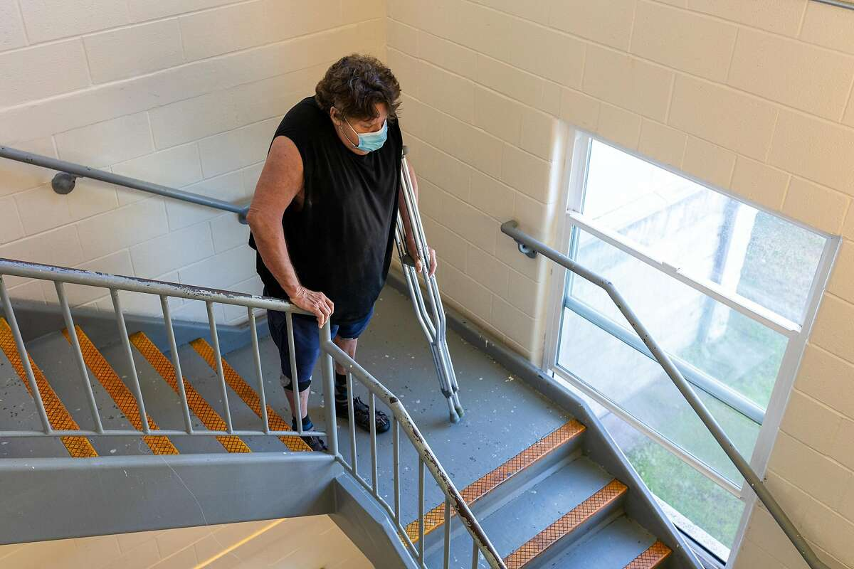 Veteran Jerry Bartlett goes down the stairs with his crutches at the Veterans Academy in San Francisco. Elevators under contruction at the veterans facility should ease the physical burden and danger of the stairs for Bartlett and other residents with mobility concerns.