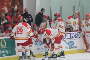 Ferris hockey players gather around the home bench on Saturday in their home game against Trine. (Pioneer photo/John Raffel)