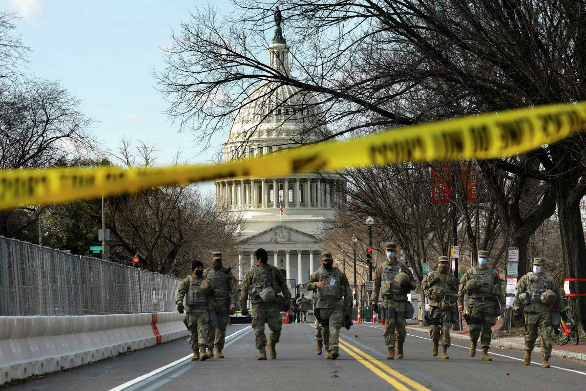 On the day before the presidential inauguration, troops guard the east side of the Capitol on Tuesday in Washington.