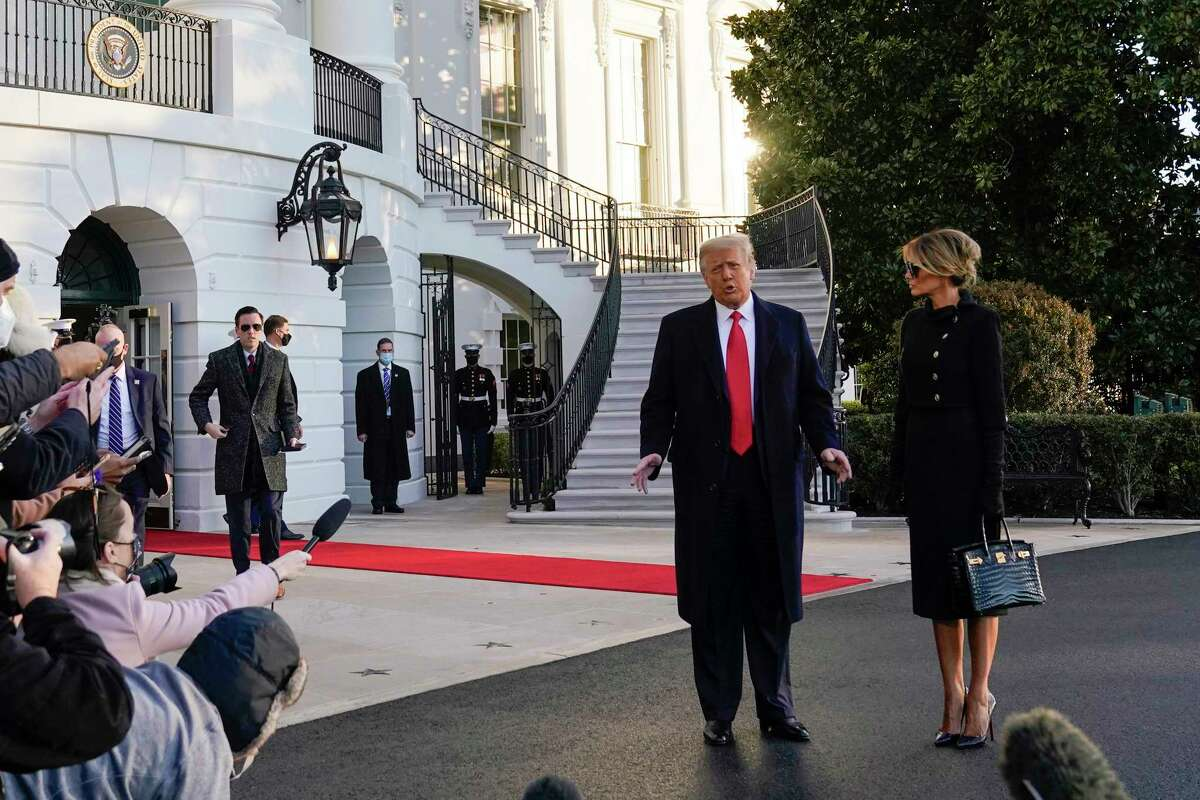 President Donald Trump and first lady Melania Trump stop to talk with the media as they walk to board Marine One on the South Lawn of the White House, Wednesday, Jan. 20, 2021, in Washington. Trump is en route to his Mar-a-Lago Florida Resort.
