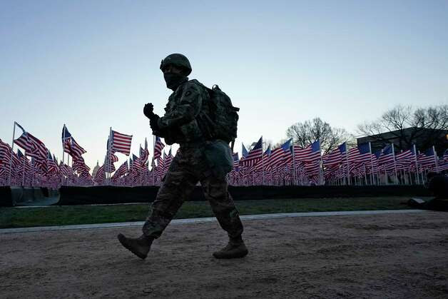 A National Guardsman walks past the flags the line the National Mall ahead of President-elect Joe Biden's inauguration ceremony, Wednesday, Jan. 20, 2021, in Washington. Photo: Julio Cortez, AP / Copyright 2021 The Associated Press. All rights reserved.
