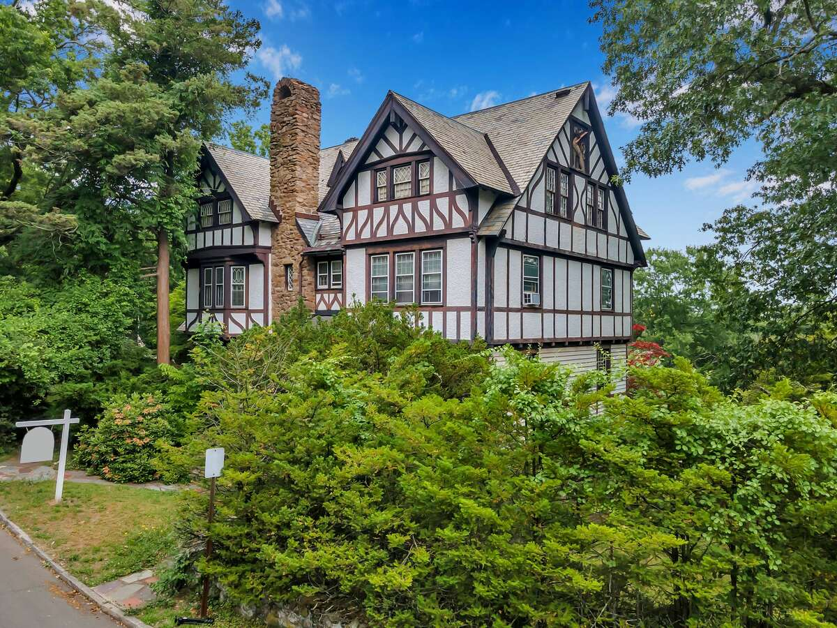 Tudor-style house at 5 St. Ronan Terrace, in a historic New Haven neighborhood. Chances are the former resident, Joan Panetti, was inspired by her surroundings within this 12-room, 6,228-square-foot house, which includes ornate hand-carved wood doors, fluted pilasters and other millwork and moldings, a decorative newel post and railings, elegant entablature, Corinthian columns, etched glass-paned French doors and four fireplaces - one of them with a floor-to-ceiling surround of in-lay details and ivory tiles. At the front entrance there is a solid iron gate depicting medallions of Tudor roses.  The house was built in 1903