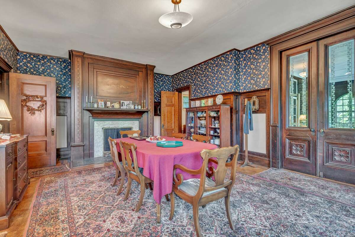 Banquet-sized formal dining room with fireplace at 5 St. Ronan Terrace, New Haven. The storybook house features a slate roof and half-timber framed exterior typical of Tudor architecture. The interior features spacious rooms, including a banquet-sized formal dining room that can accommodate intimate family dinners and large-scale entertaining. Outside, this property features a covered deck and garden area.