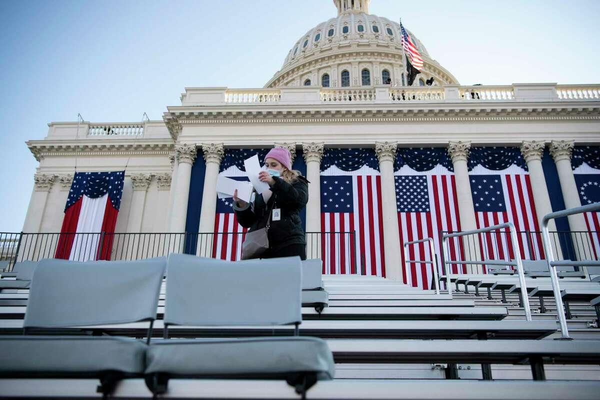 A volunteer looks at name cards as preparations are made ahead of President-elect Joe Biden's inauguration ceremony, Wednesday, Jan. 20, 2021, in Washington. (Caroline Brehman/Pool Photo via AP)