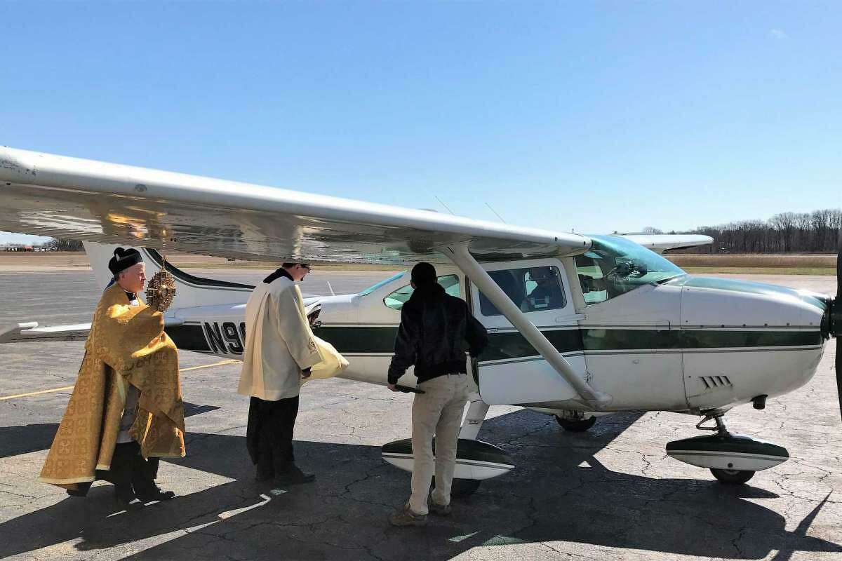 The Rev. Brian Gannon of St. Theresa Roman Catholic Church in Trumbull and the Rev. Flavian Bejan, associate pastor, prepare to board a Cessna 172 plane at Sikorsky Memorial Airport before flying over the Bridgeport Diocese to bestow blessings March 24, 2020.