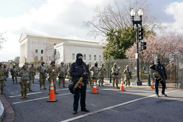 WASHINGTON, DC - JANUARY 20: Members of the National Guard and law enforcement gather near the U.S. Capitol before the inauguration of U.S. President-elect Joe Biden and Vice President-elect Kamala Harris on January 20, 2021 in Washington, DC. (Photo by Nathan Howard/Getty Images) Photo: Nathan Howard/Getty Images / 2021 Getty Images