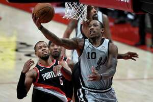 San Antonio Spurs forward DeMar DeRozan, right, drives to the basket on Portland Trail Blazers guard Rodney Hood, right, during the second half of an NBA basketball game in Portland, Ore., Monday, Jan. 18, 2021. (AP Photo/Steve Dykes)