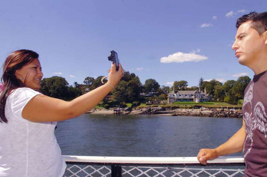 Adrianna Morocho, 25, of Tarrytown, N.Y., takes a photograph of her brother, Paul Morocho, on the Island Beach ferry, on Sunday, Sept. 5, 2010. Photo: Helen Neafsey / Greenwich Time