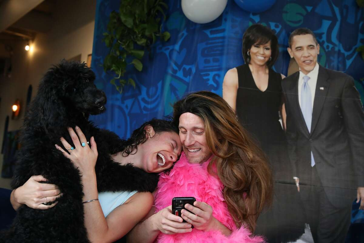 Rebecca Lozano, left, and Rob Avruch react as Avruch's dog Luna joins in while watching the inauguration at a virtual inauguration event at Manny's Cafe on Wednesday, January 20, 2021 in San Francisco, Calif.
