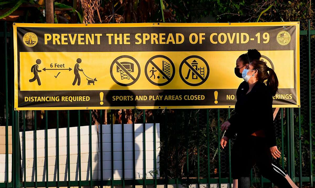 Pedestrians wearing face masks walk past a prevent the spread of Covid-19 banner in Los Angeles in January.