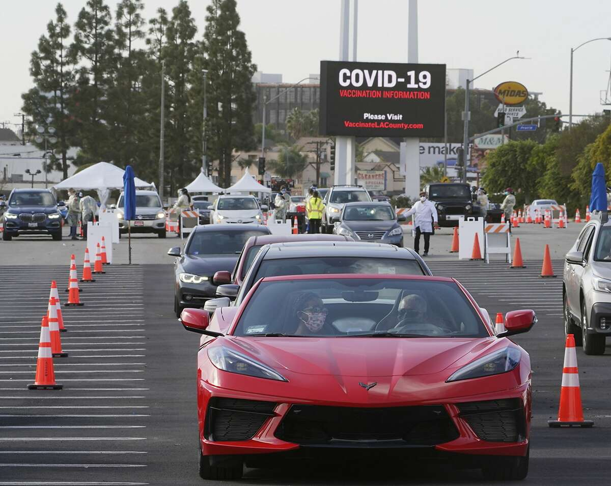 People wait in their vehicles to monitor for adverse reactions to the shot after being vaccinated at a mass COVID-19 vaccination site outside The Forum in Inglewood, Calif., Tuesday, Jan. 19, 2021.