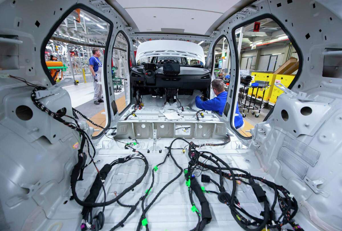 A worker completes an electric car ID.3 body at the assembly line, during a press tour at the plant of the German manufacturer Volkswagen AG, VW, in Zwickau, Germany. Automaker Volkswagen tripled sales of battery-only cars last year as its new electric compact ID.3 came on the market ahead of tough new limits on auto emissions.