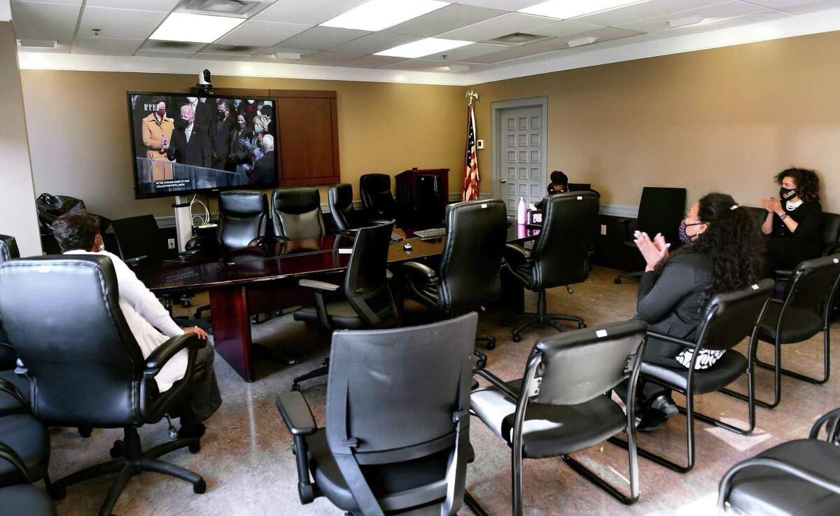 Staff of the Elm City Communities Housing Authority of New Haven watch the inauguration of President Joseph Biden while keeping socially distant in the Housing Authority boardroom in New Haven Jan. 20, 2021.