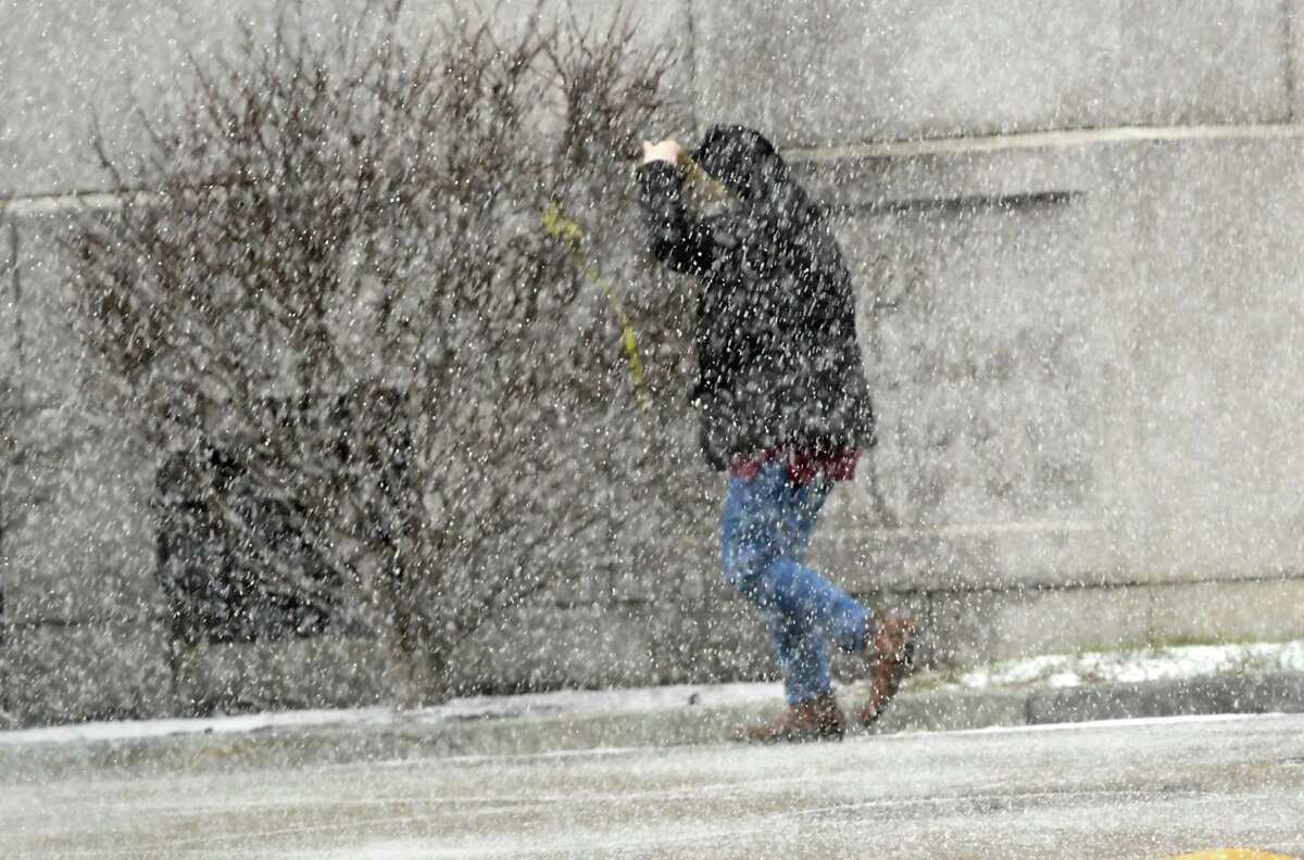 Be sure to bundle up Tuesday: The National Weather Service predicts a snowstorm will drop about 4 inches of snow on the Albany area and slightly more in the southern Adirondack Mountains. In this photograph, a pedestrian holds on to the hood of their jacket during a windy snow squall on last week in Albany. (Lori Van Buren/Times Union)