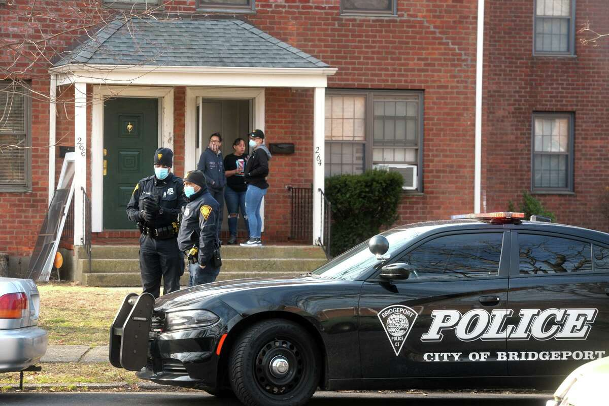 Police and neighbors look on near the scene of a fatal stabbing that happened overnight on Pennsylvania Ave., in Bridgeport, Conn. Jan. 20, 2021.