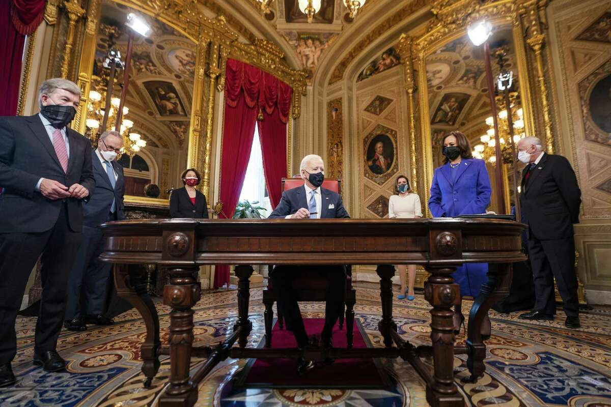 U.S. President Joe Biden, center, signs documents in the President's Room at the U.S. Capitol following the 59th presidential inauguration ceremony in Washington, D.C., U.S., on Wednesday, Jan. 20, 2020. Biden will propose a broad immigration overhaul on his first day as president, including a shortened pathway to U.S. citizenship for undocumented migrants - a complete reversal from Donald Trump's immigration restrictions and crackdowns, but one that faces major roadblocks in Congress. Photographer: Jim Lo Scalzo/EPA/Bloomberg