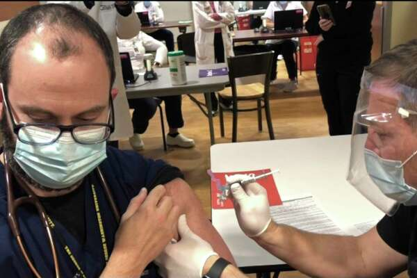 Dr. Guillermo Ballarino, pulmonary intensivist, gets the first COVID-19 vaccine at Danbury Hospital. Dr. Ballarino has been on the frontlines caring for patients since Danbury Hospital's first COVID-19 patient in March.