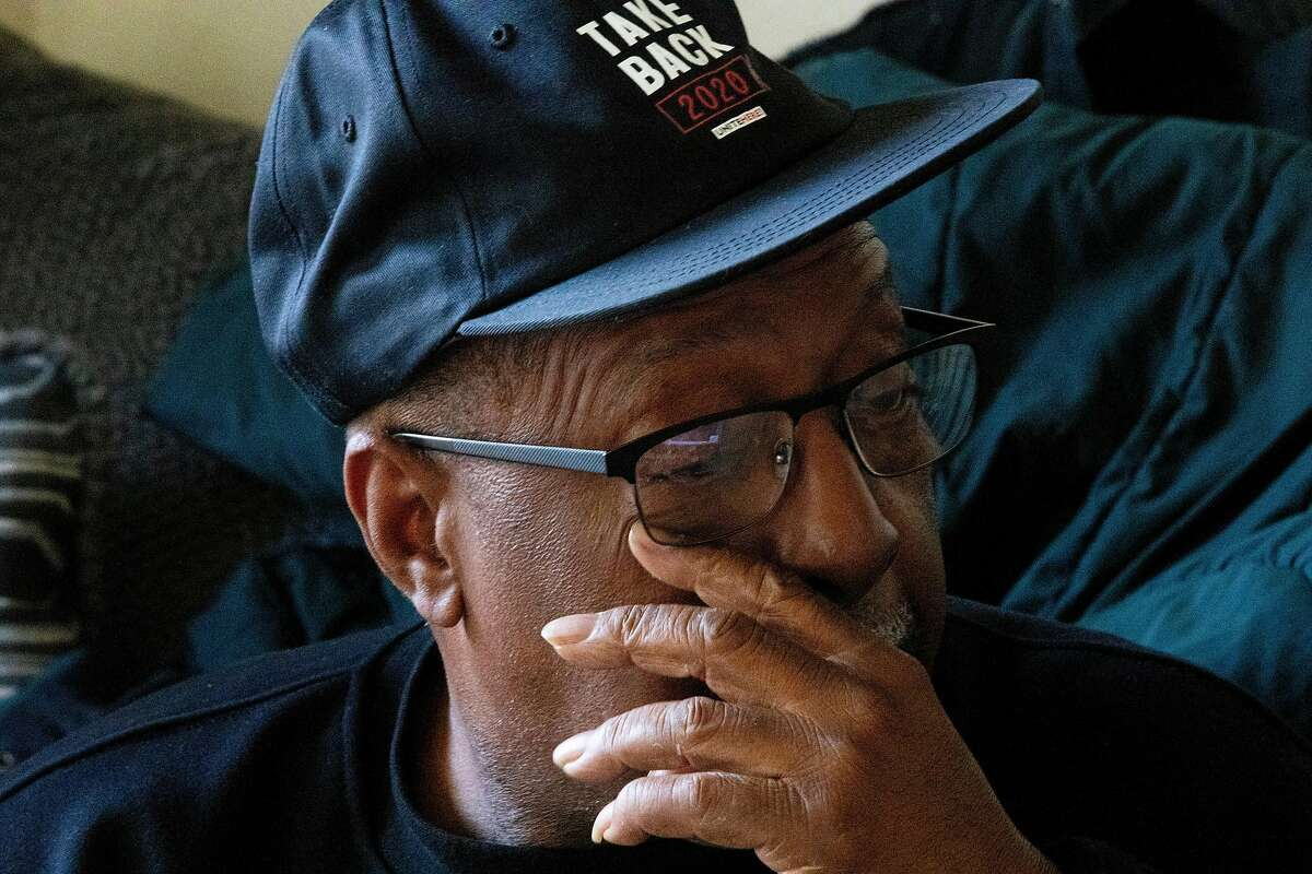 Tony Evans, a furloughed bartender at Chase Center, wipes away a tear while watching the inauguration of Joe Biden and Kamala Harris with his granddaughter Dy'mond Roberts while at his daughter's apartment in East Oakland, Calif. Wednesday, January 20, 2021. Evans flew to Georgia to work as a poll worker during the elections.