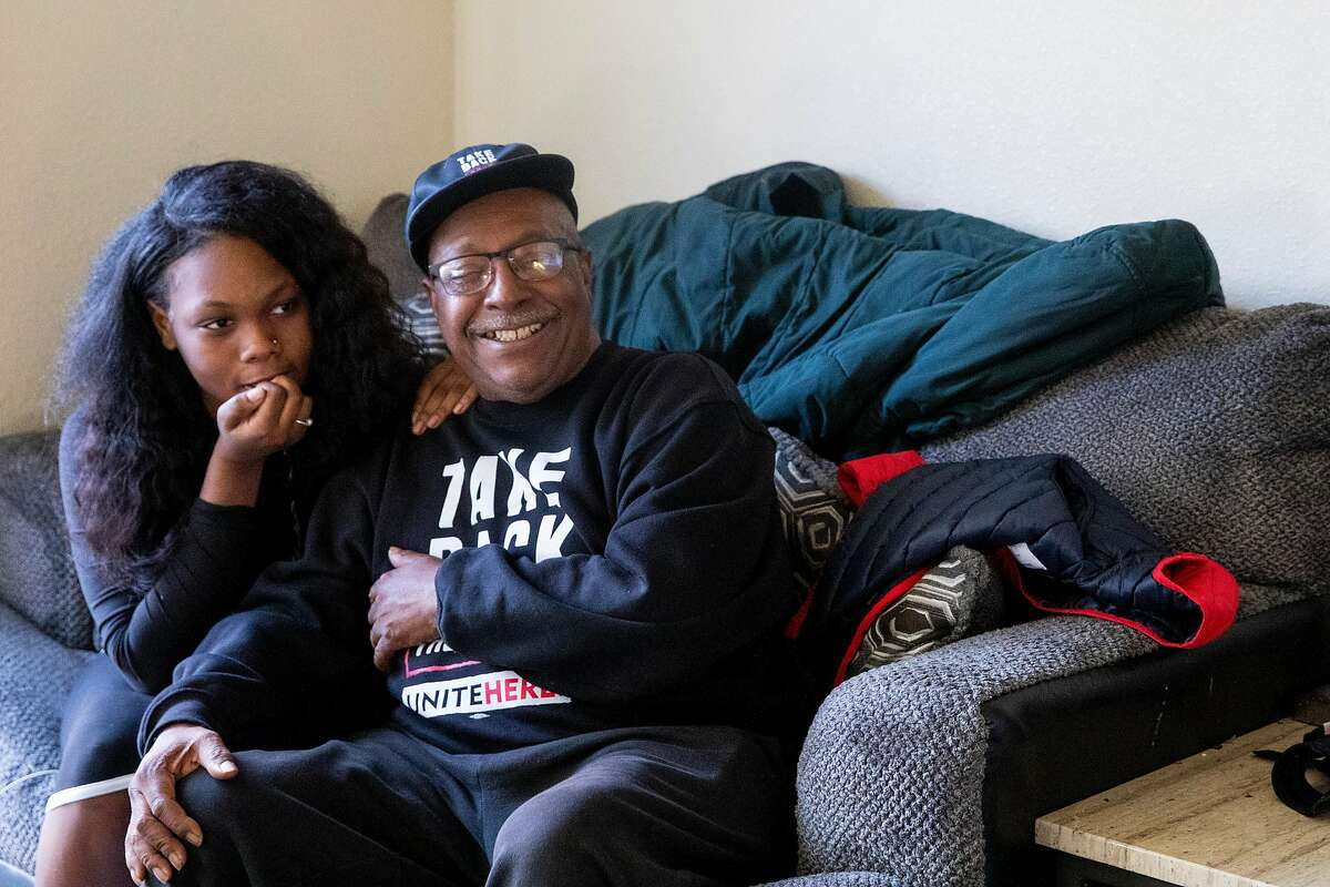 Tony Evans, a furloughed bartender at Chase Center, watches the inauguration of Joe Biden and Kamala Harris with his granddaughter Dy'mond Roberts while at his daughter's apartment in East Oakland, Calif. Wednesday, January 20, 2021. Evans flew to Georgia to work as a poll worker during the elections.