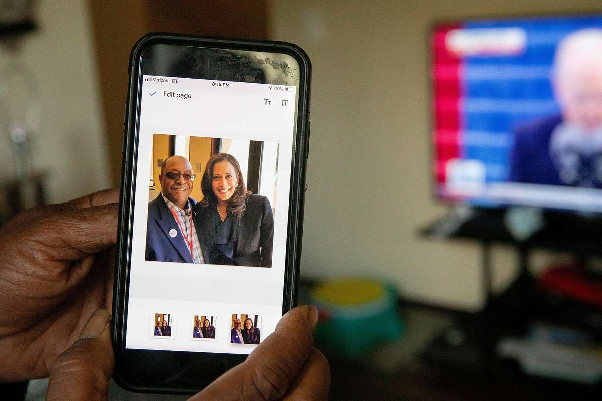 Tony Evans, a furloughed bartender at Chase Center, shares a picture of himself and Oakland native Kamala Harris before watching the inauguration of Joe Biden and Kamala Harris with his granddaughter Dy'mond Roberts while at his daughter's apartment in East Oakland, Calif. Wednesday, January 20, 2021. Evans flew to Georgia to work as a poll worker during the elections.