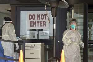 Stamford Hospital nurses wear protective gowns, gloves and masks in an area outside the hospital that had been set up to test for the COVID-19 virus in Stamford, Connecticut on March 17, 2020.