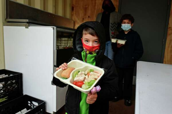 J.J. Santamaria, 5, looks at a portion of grilled chicken salad at the Norwalk Public Schools meal distribution site at Colonial Village Tuesday, January 19, 2021, in Norwalk, Conn.