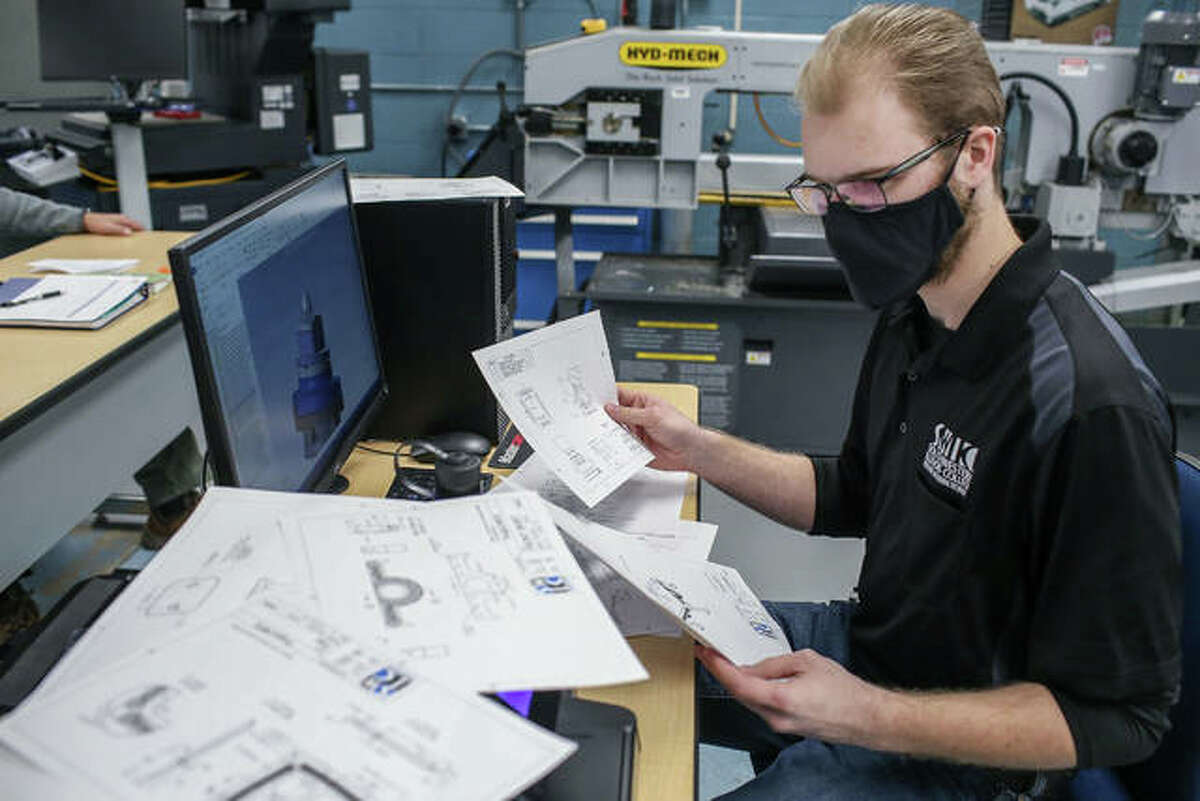 Southwest Illinois College's Gavin Becherer of Troy operates a 5-axis CNC mill to create a machine part designed by his team for the Department of Defense Advanced Manufacturing contest.