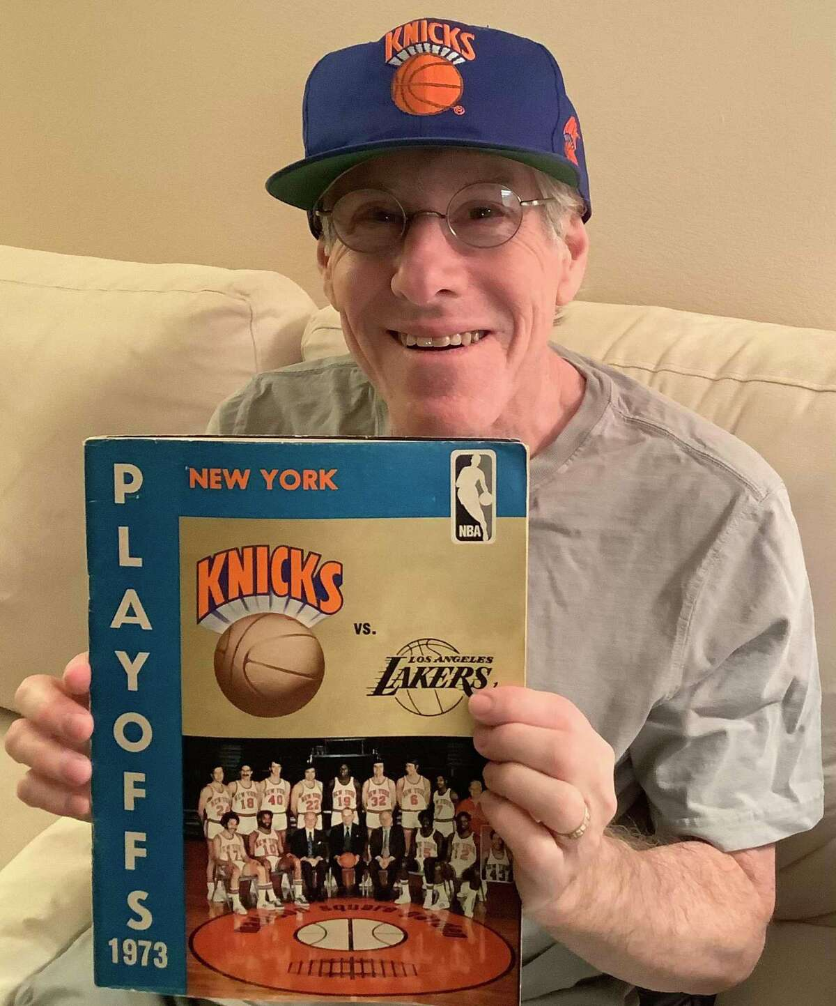Fred Cantor wearing a hat with a vintage Knicks logo and holding the playoff program from the 1973 NBA Finals, the last time the Knicks won the NBA championship.
