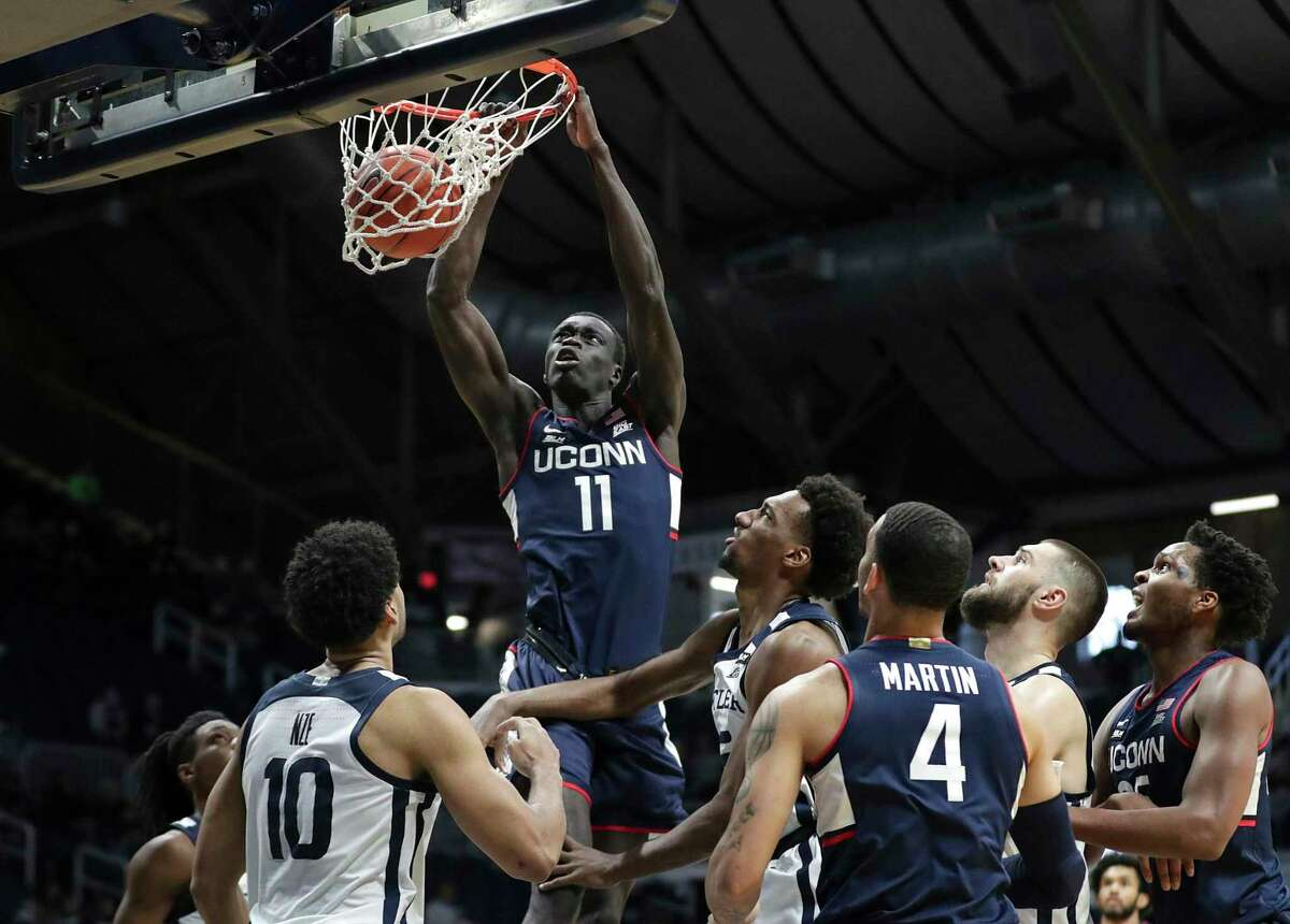 Connecticut forward Akok Akok (11) dunks against Butler in the first half of an NCAA college basketball game on Saturday, Jan.9, 2021 in Indianapolis.  (Jenna Watson / The Indianapolis Star via AP)