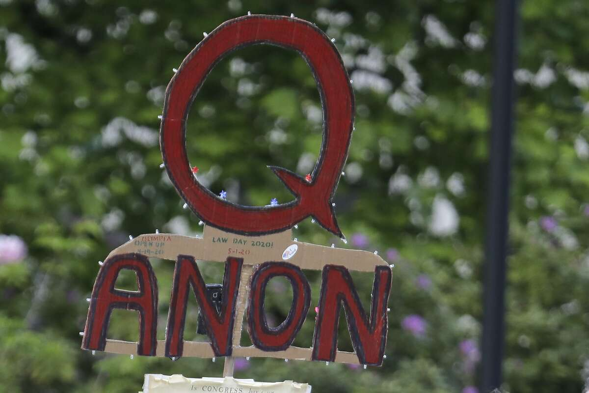 FILE - In this May 14, 2020 photo, a person carries a sign supporting QAnon during a protest rally in Olympia, Wash.