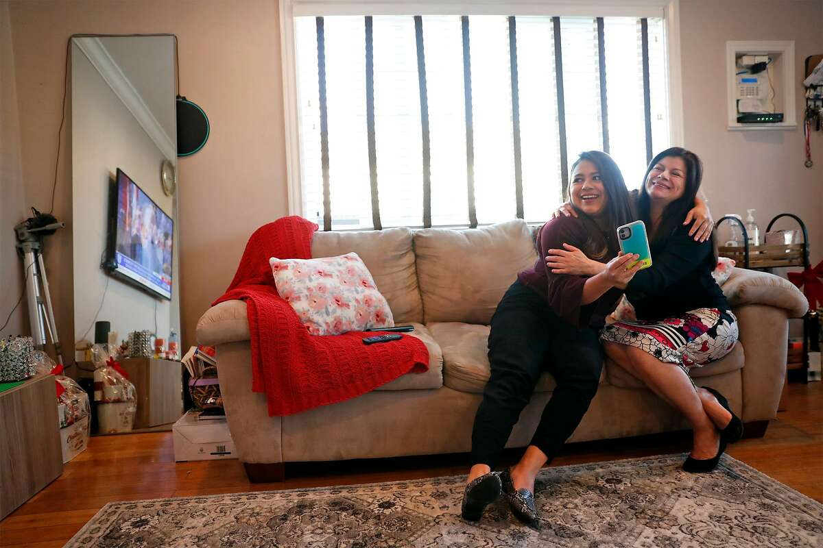 DACA recipient Vanessa Mejia and her mother, Conie, watch from their living room in Oakland, Calif., as US President Joe Biden takes the oath of office at the US Capitol in Washington, DC on Wednesday, January 20, 2021.