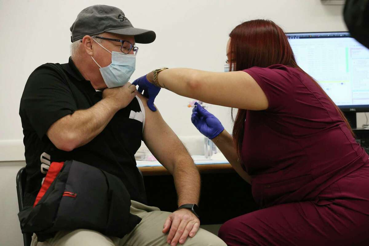 Jay Flexner, 59, gets the Moderna COVID-19 vaccine administered by Maribel Hernandez at Wonderland of Americas Mall, Monday, Jan. 4, 2021. People lined up for the vaccine administered by University Health. It is the first day of vaccinating people in the 1B group, those 65 years and over and 18 and above with certain medical conditions. The 17,280 vaccination slots were taken up in five hours after University Health opened the website for registration on Dec. 31.