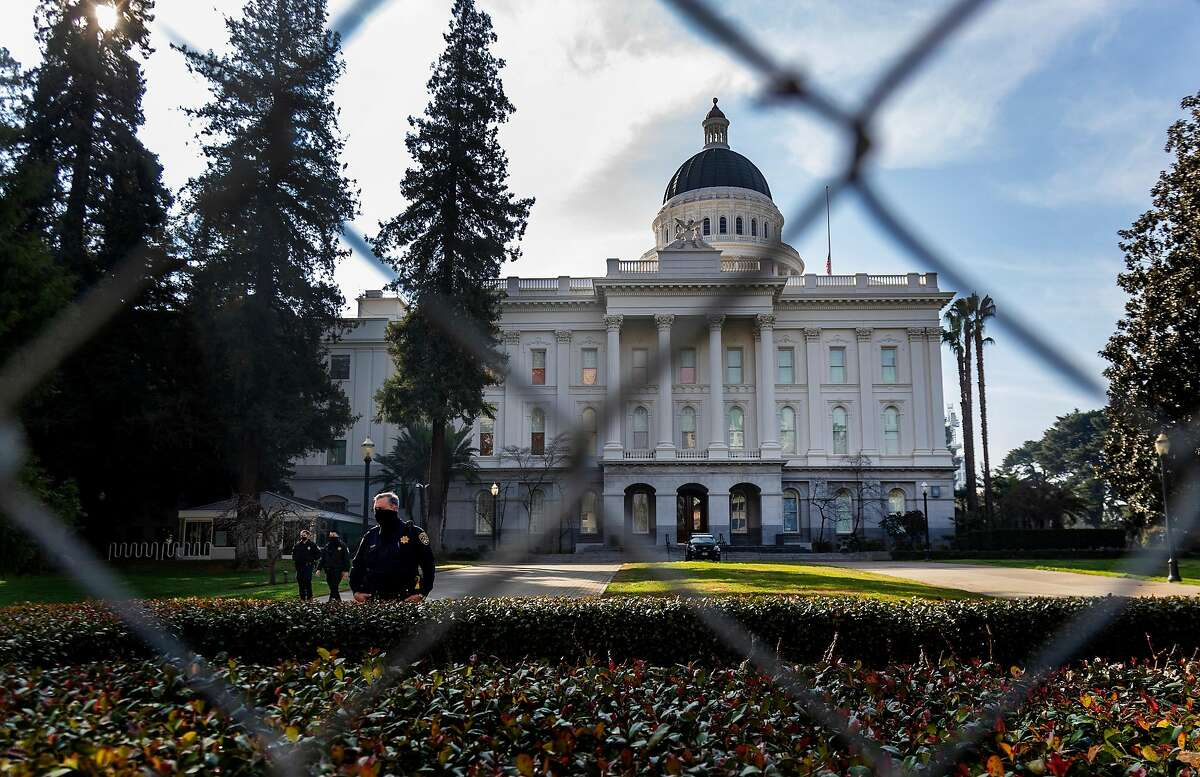 California Highway Patrol officers stand guard in front of the State Capitol behind a six-foot high fence in anticipation of possible civil unrest this weekend by supporters of President Donald Trump, on January 15, 2021, in Sacramento, California. (Gina Ferazzi/Los Angeles Times/TNS)