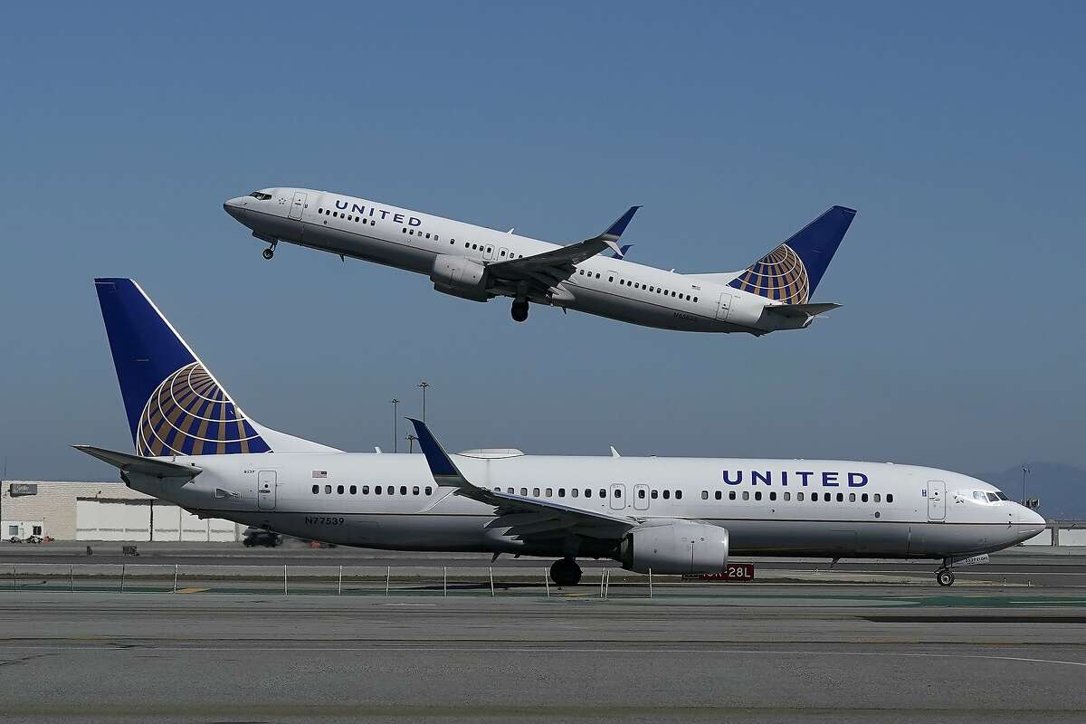 A United Airlines airplane takes off over another United plane on the runway at San Francisco International Airport in San Francisco.