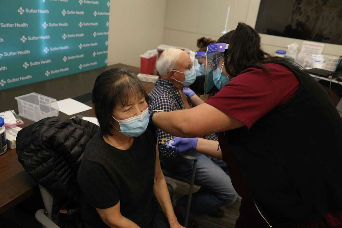 Kay Whitecotton and Tom Whitecotton, a Sonoma husband and wife of 56 years, receive the Moderna COVID-19 vaccination at a San Francisco Sutter Health clinic for seniors 75 and older.