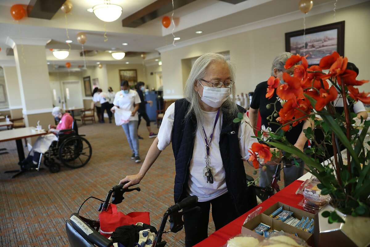 Virginia Quong, 77, admires the tables set up with food and snacks for available for residents after they received Pfizer COVID-19 vaccinations at a vaccine clinic at the senior living community in Daly City. CVS administered the vaccine clinic.