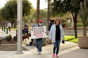 Danny Meehan holds a protest sign as he and Pamela Meehan walk past members of the news media outside the Arizona Capitol in Phoenix on Wednesday, Jan. 20, 2021.