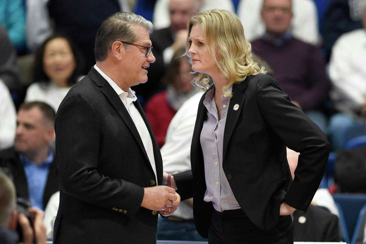 UConn coach Geno Auriemma, left, talks with Tennessee coach Kellie Harper before a game in Hartford last January.